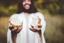 Closeup Shot Of Jesus Christ Handing Out Bread With A Blurred Background