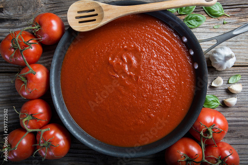 Photo  Tomato sauce in pan with wooden spatula and ingredients