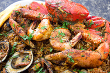 Close Up Of Seafood With Rice In A Black Marble Background. Delicious Ecuadorian Dish With Crab, Shrimps, Mussels, Fried Banana And Rice.