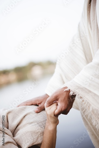 Slika na platnu Vertical shot of Jesus Christ healing the female with a blurred background