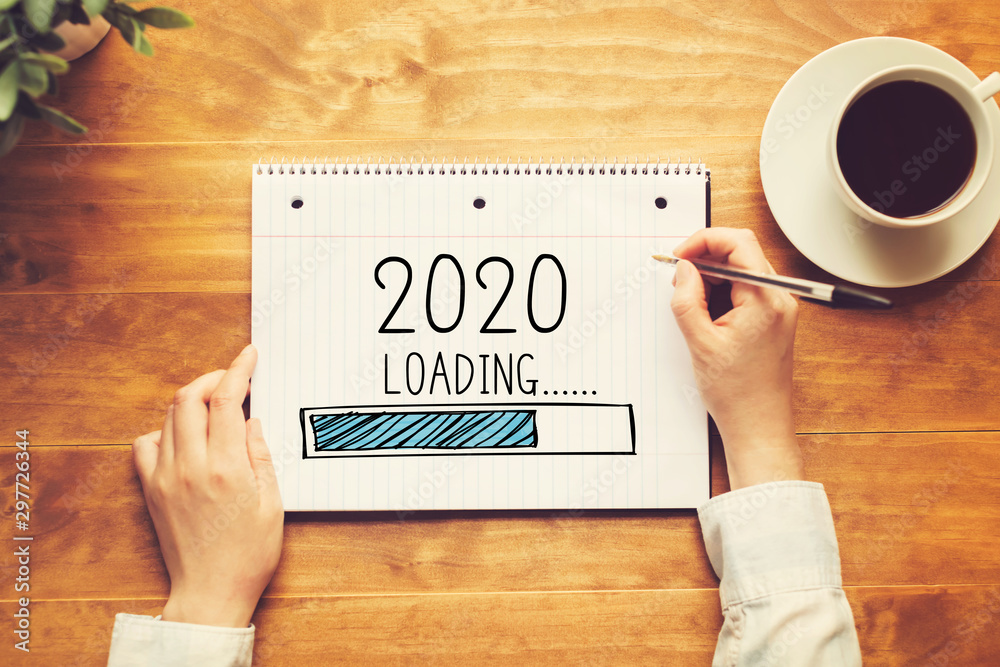 Loading new year 2020 with a person holding a pen on a wooden desk