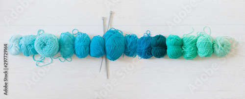Yarn for knitting aquamarine, green, blue and turquoise colors. White wood long background