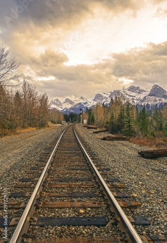 Fotografía Canadian Pacific Railway Line and Distant Mountain Peaks Landscape against Drama