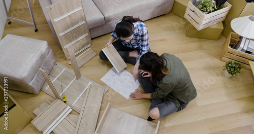 Fotografie, Tablou  top view two young lesbian couple installing assembly furniture in new house with instructions paper