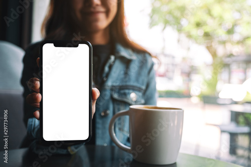 Obraz Mockup image of a beautiful woman holding and showing black mobile phone with blank screen in cafe - fototapety do salonu