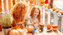 Happy Woman Drawing On Pumpkin With Her Little Daughter