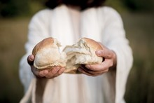 Closeup Shot Of Jesus Christ Splitting The Bread With A Blurred Background