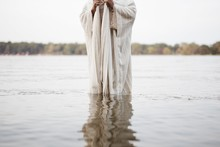 Person Wearing A Biblical Robe Standing In The Water With A Blurred Background
