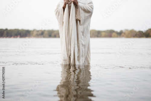 Person wearing a biblical robe standing in the water with a blurred background Fototapet