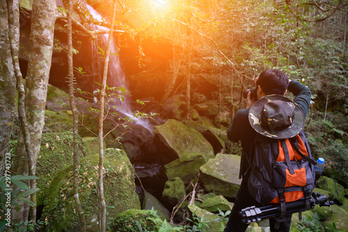 Photo sur Aluminium Marron Male photographer traveling and photographing waterfalls in the mountains