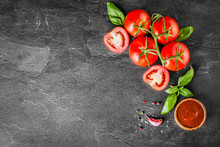 Fresh Tomatoes With Basil On Dark Stone Table Top View. Vegetables Tomato With Ketchup In Bowl On Board.
