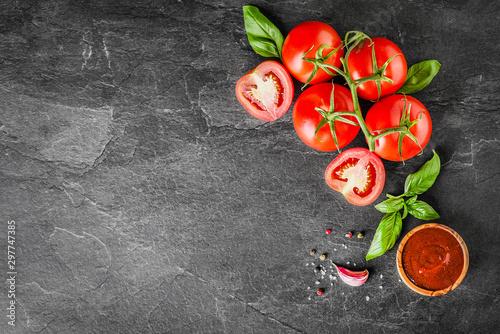 Obraz na płótnie Fresh tomatoes with basil on dark stone table top view