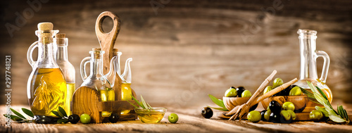 Fototapeta Fresh olives in rustic bowls on old wooden table. Virgin olive oil in clear glass bottles copy space.  Panorama or banner concept. obraz