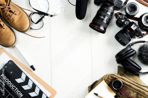 Fototapeta Camping or adventure trip scenery concept. Backpack, boots, belt, thermos and camera on wooden background captured from above (flat lay). Layout with free text (copy) space. obraz na płótnie