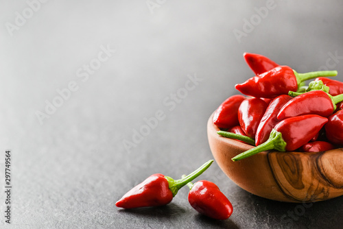 Canvas Prints Hot chili peppers Hot pepper in wooden bowl on dark stone table. Chili red peppers and green leaves on black background.