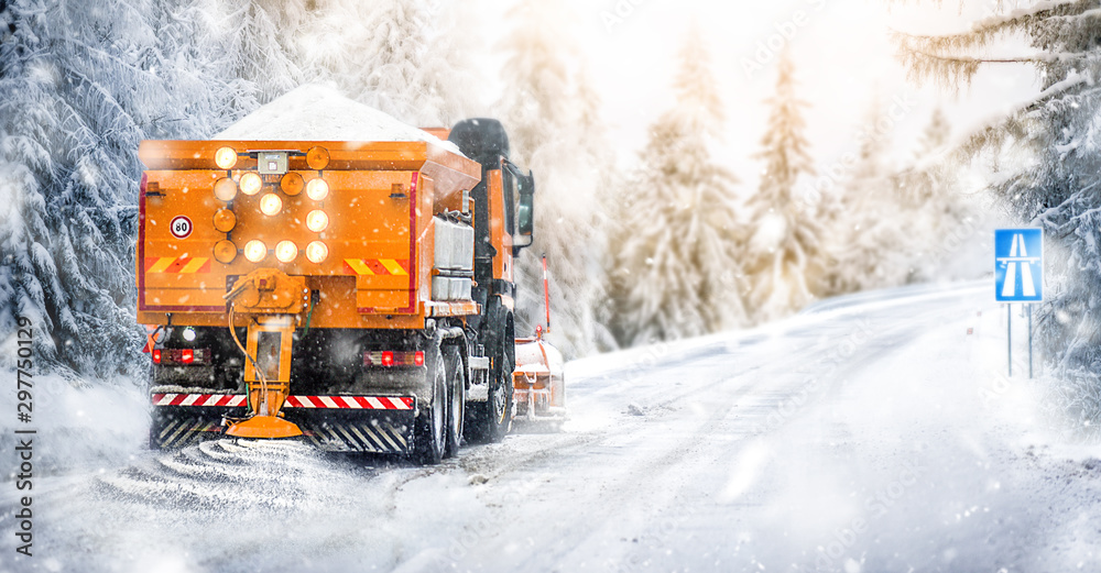 Fototapety, obrazy: Salting highway maintenance. Snow plow truck on snowy road in action. Hard weather condition in winter. Vehicle spreading deicing salt.