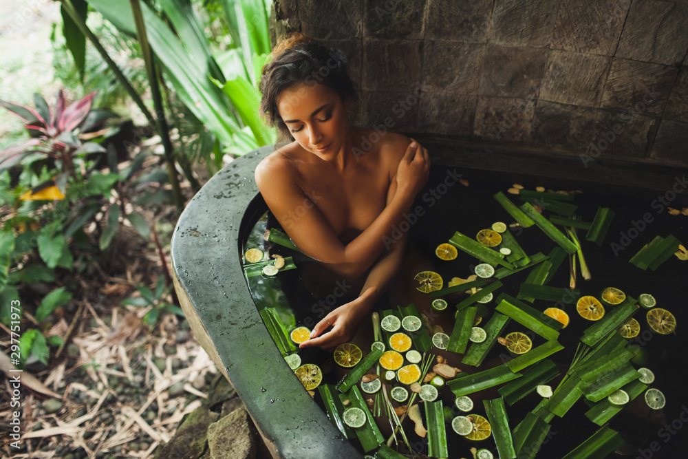 Fototapety, obrazy: Beautiful young woman enjoying in outdoor spa. Luxury stone bath tub with jungle view. Natural organic tropical ingredients in the water: ginger, lime, orange and sea salt. Beauty treatment concept.