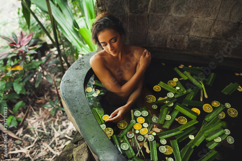 Montage in der Fensternische Spa Beautiful young woman enjoying in outdoor spa. Luxury stone bath tub with jungle view. Natural organic tropical ingredients in the water: ginger, lime, orange and sea salt. Beauty treatment concept.