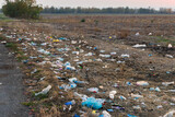 Fototapeta Sport - Pollution of the environment,  trash left in the meadow. Global pollution