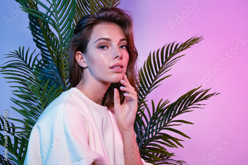 Obraz Beautiful female touching face with tenderness. Lady sitting near green palm tree and looking at camera with tenderness. Beauty and fashion concept - fototapety do salonu