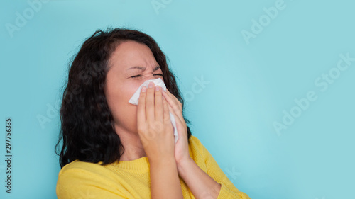 Young woman with cold blowing her runny nose Tablou Canvas