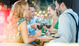 People in a restaurant eating and drinking red wine