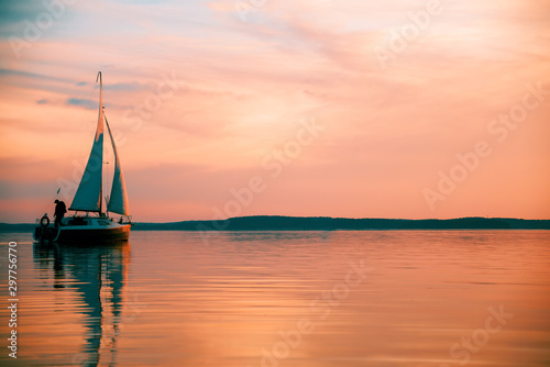 Sailing boat floats on the lake at sunset. Fotobehang