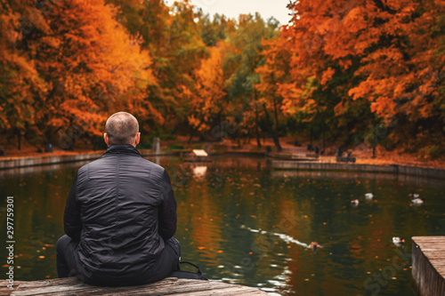 Fototapety, obrazy: Alone man sits beside a pond in the park. Autumn background.
