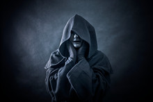 Ghostly Figure In Hooded Cloak. Scary Figure With Part Of Mannequin Head In Hands