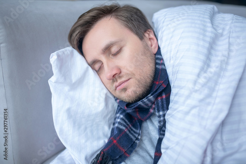 Poster de jardin Echelle de hauteur Bearded man sleeping while having high body temperature