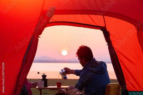 Foto auf Gartenposter Rot Camping tent,Morning coffee and nature Sunrise inside a Tent,Tourists pour coffee from Mocha Pot, a beautiful sunrise,