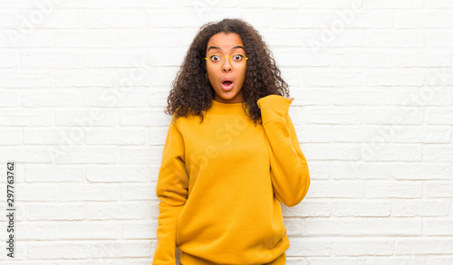 Fotografía  young black woman looking astonished in disbelief, pointing at object on the sid
