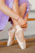 Close up for ballet dancer putting on, tying ballet shoes. Ballerina putting on her pointe shoes.