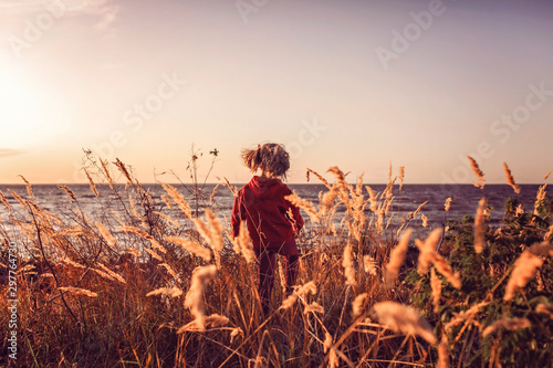 Fotografie, Tablou  Adorable girl looking at the sunset on the sea