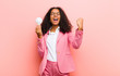 young black pretty woman with a light bulb having an idea against pink wall background