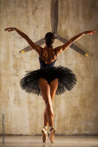 Fotografía Young beautiful ballerina in black ballet tutu posing in dark studio