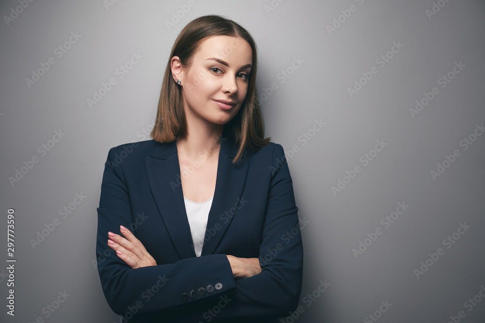 Fototapeta Confidence and charisma. Young business woman in suit looking at camera. Grey background.