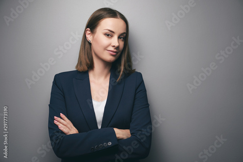 Confidence and charisma. Young business woman in suit looking at camera. Grey background.