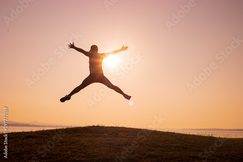 Foto auf Gartenposter Frühling silhouette of Jumping Man on the peaks and backgrounds of sunrise or sunset,men trail running, the sky at sunrise running in the mountains, lifestyle