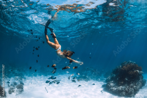 Fotomural  Young woman free diver in bikini glides over sandy sea with fishes
