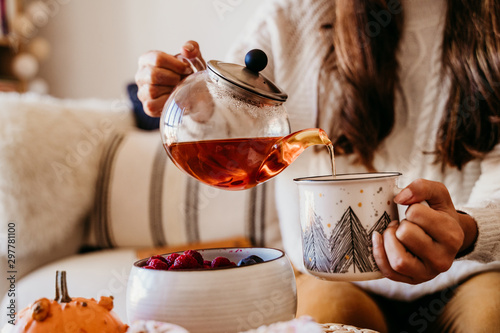 Obraz woman having a cup of tea at home during breakfast. Cute golden retriever dog besides. Healthy breakfast with fruits and sweets. lifestyle indoors - fototapety do salonu