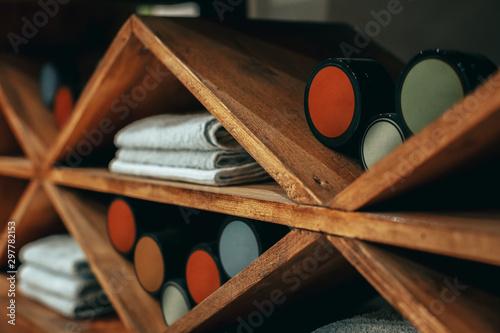 Creams and towels lie on wooden slanting shelves in brown tones