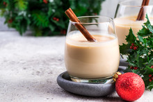 New Year Or Christmas Eggnog Cocktail With Cinnamon And Nutmeg In A Glass, Branches Of Holly Berries And Ball Toy On Light Stone Background, Festive Decoration