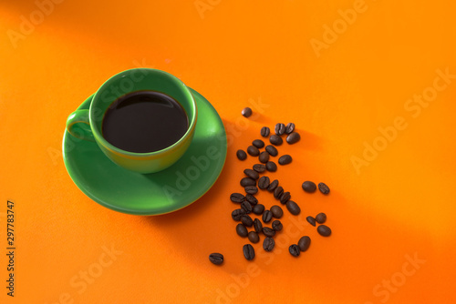 Fotografia, Obraz Green cup of coffee with roasted coffee beans on orange background