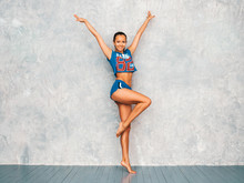 Portrait Of Fitness Woman In Sports Clothing Looking Confident.Young Female Wearing Sportswear. Beautiful Model With Perfect Tanned Body.Female Stretching Out Before Training Near Gray Wall In Studio