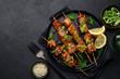 Leinwandbild Motiv Teriyaki salmon skewers on black plate
