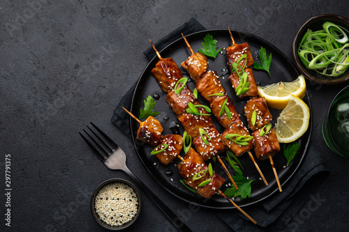 Fotomural  Teriyaki salmon skewers on black plate