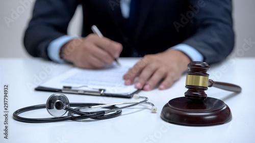 Photo Judge signing arrest warrant for medical error, banging gavel near stethoscope