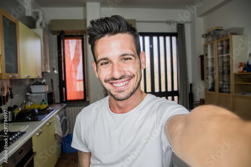 Cuadros en Lienzo Photo of handsome man taking a selfie at home smiling on the camera