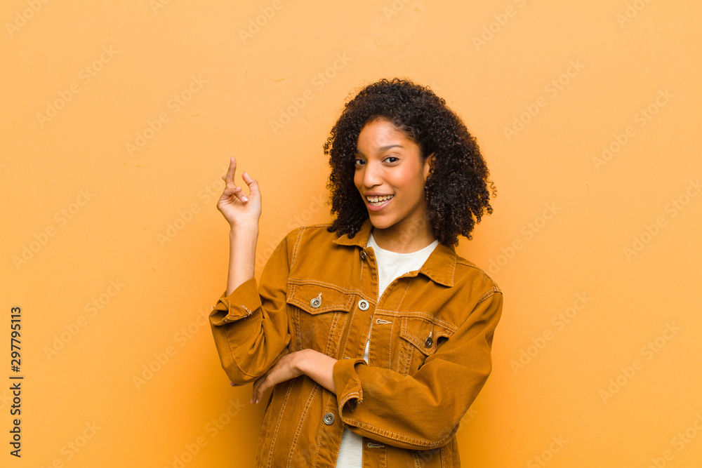 Fototapety, obrazy: young pretty black woman smiling happily and looking sideways, wondering, thinking or having an idea against orange wall